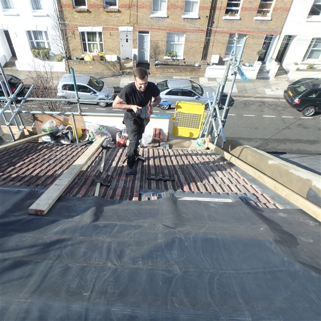 Adjusting the concrete tiles on this mansard conversion in Orbain Road - SW6