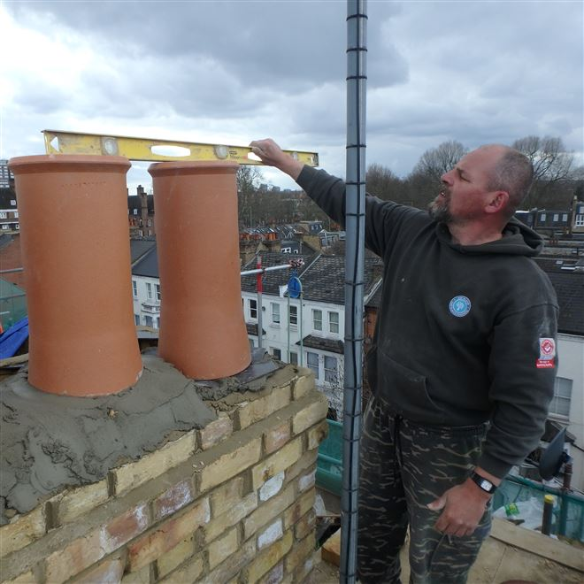 John in Harwood Road checking the Spirit Levels for the New Chimney - Fulham