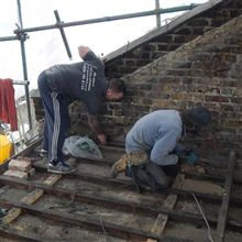 Anthony and Brian cutting pockets in the party wall for the steel bearer plates
